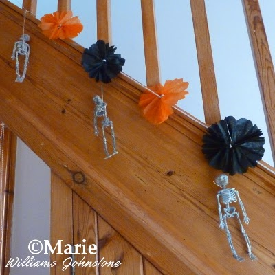 Orange and black tissue decoration hung on the staircase with skeletons