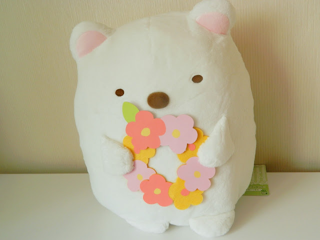 A photo of a polar bear plush from the Japanese franchise Sumikko Gurashi. It is holding a colouring flower crown