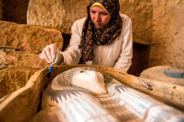 An excavation worker works inside a burial shaft at the Giza pyramid plateau