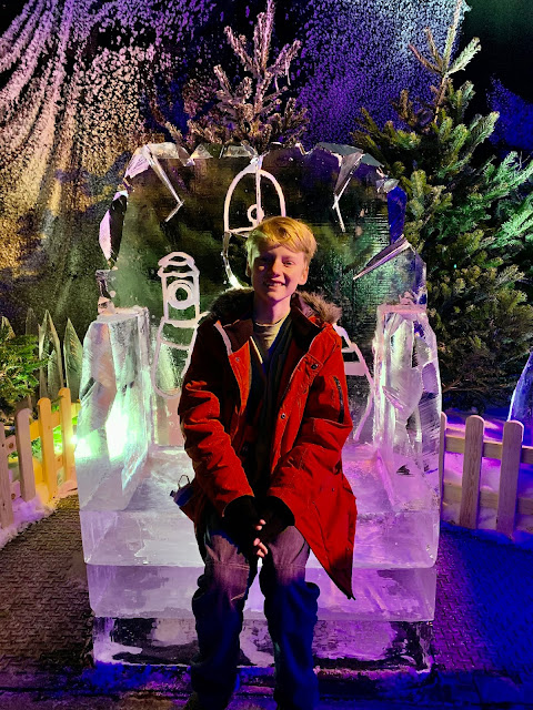 Teenage boy sits in ice chair sculpture at Magical Ice Kingdom, Winter Wonderland, Hyde Park, 2019