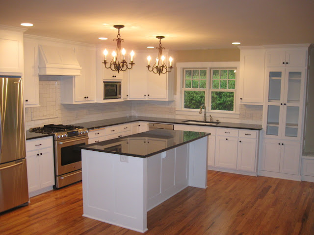 white painted kitchen cabinets with lighting and icebox