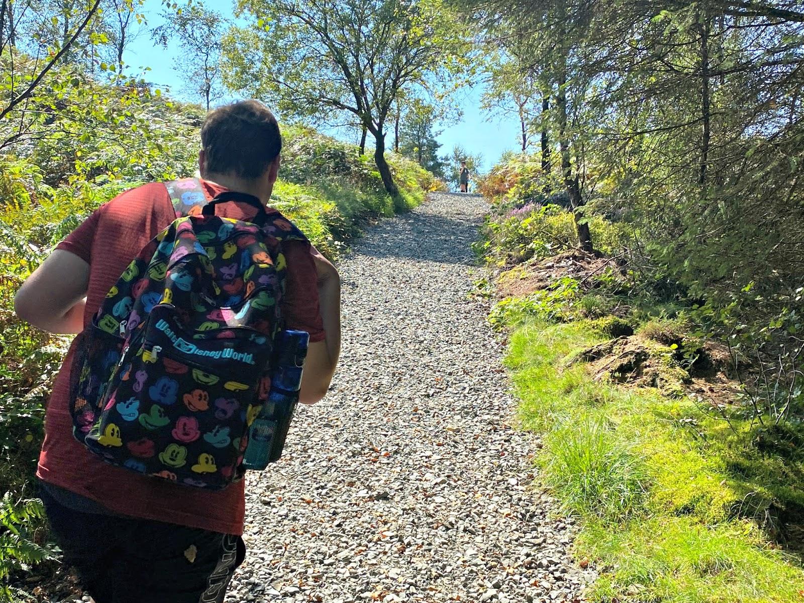 A boy walking up a steep hill