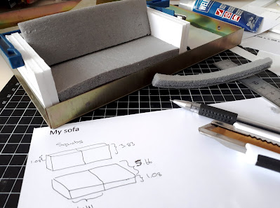 One twelfth scale modern miniature sofa in a gluing jig, with clamps holding the sides to the back. There are squab pieces cut out of foam inserted into it, and the measurements for the squab pieces worked on on a paper in front.