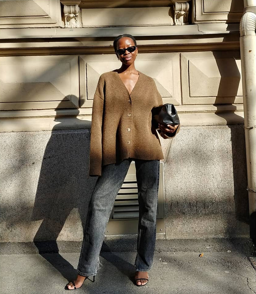 Laid-Back Yet Elevated Fall Outfit Idea — Sylvie Mus in a brown cardigan , black jeans, strappy heeled sandals, '90s-inspired sunglasses, and Demellier London bag