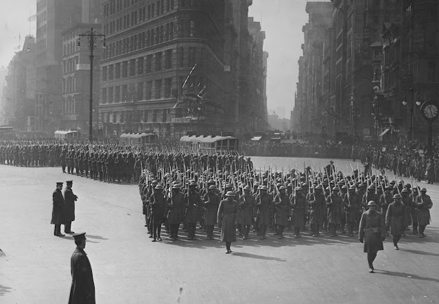 Original caption: Parade of returned fighters of the famous 369th colored Infantry at the Flatiron building in New York City.