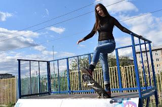 Девушка со скейтом на рампе для скейтборда