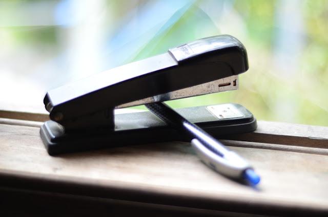 imagem de grampeador e caneta na janela do escritório de HojenaWeb Sites e SEO
