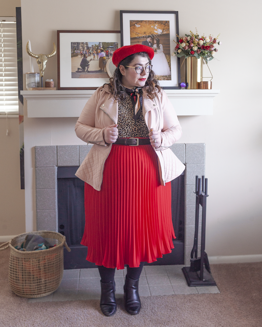 An outfit consisting of a red beret, pink peplum faux leather jacket, brown animal print top tucked unto a red pleated midi skirt and black chelsea boots.