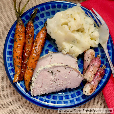overhead image of a plate of roasted carrots with fresh dill, mashed potatoes, and roast pork