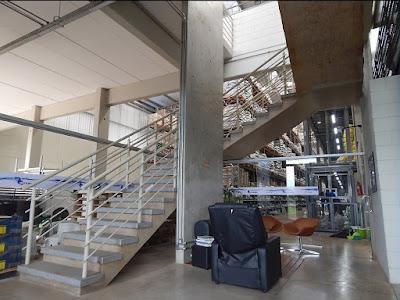 A escadaria diante do hall de recepção tem espaço reservado para um elevador de pedestres a ser estruturado na empena lateral de concreto armado aparente.