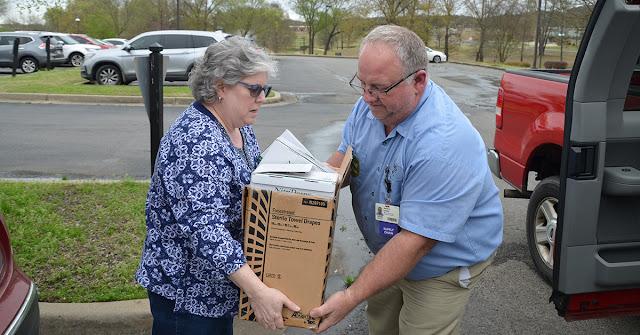 woman handing box to man