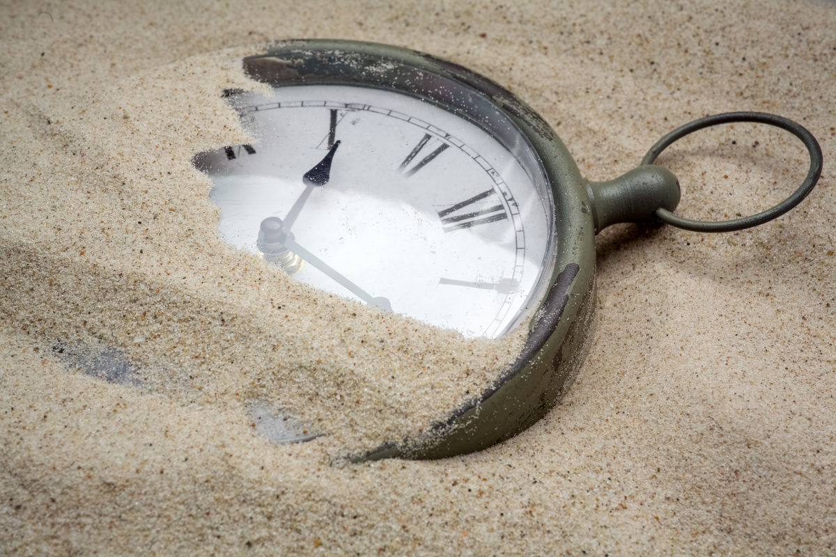An antique hand watch in the drifting sands of time