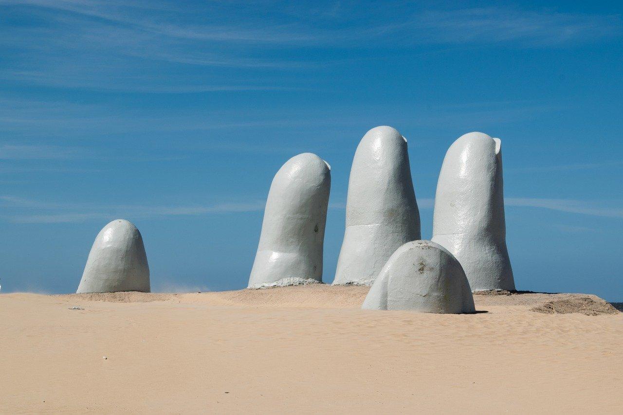 monumento la mano com 5 dedos de concreto saindo da areia da praia