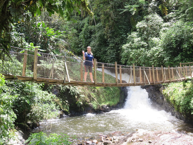 Me crossing a bridge over the river, pretty near the waterfall.