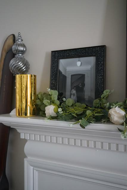 Rose garland, gold glass globe, and candlesticks on mantel