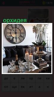 орхидеи в вазе стоят в комнате на столе и горят свечи