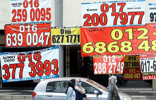 Hit hard: Covid-19 has left a wide swathe of destruction in its wake in Malaysia too. Banners of property for sale in front of a row of closed shops in Kuala Lumpur.