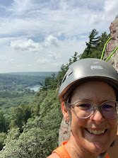 I am smiling and wearing a helmet. Behind me are bluffs and a lake well below me. There is a forest below full of green trees. The sky is blue with some white puffy clouds.