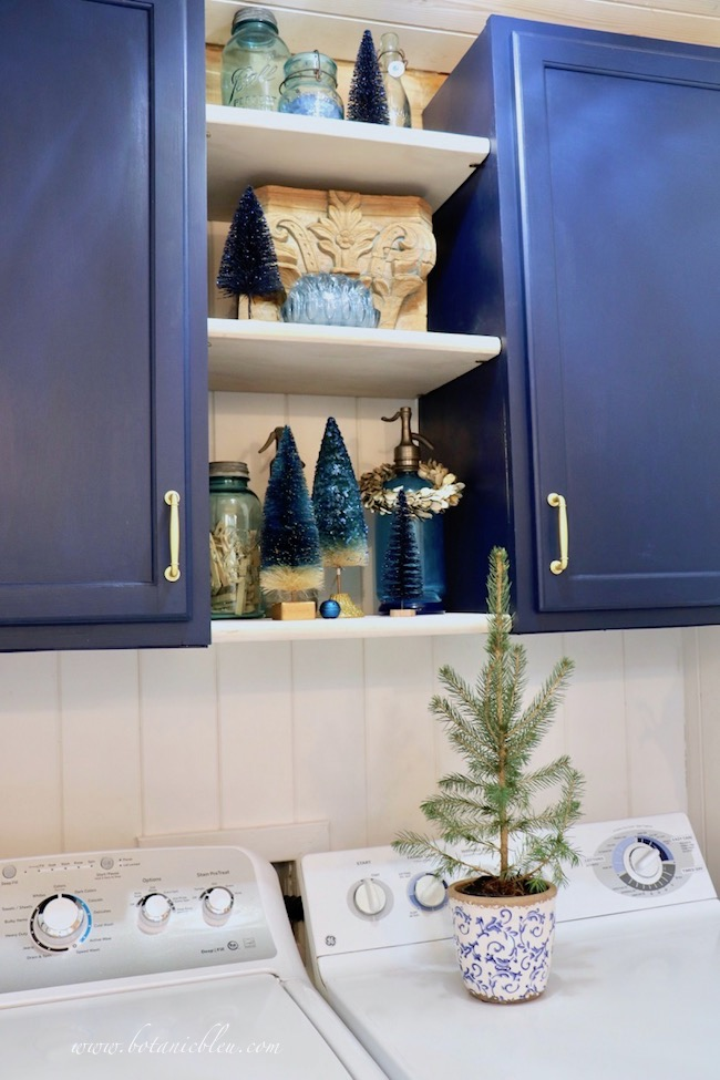 Blue Christmas Laundry Room open shelves decorated with blue bottle brush trees to match navy cabinets