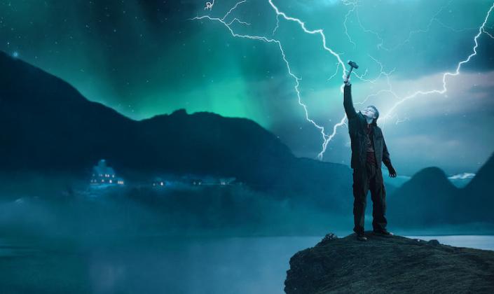 Imagem de capa: fundo com uma cidadezinha debaixo de montanhas, o céu tomado por tons de verde e azul e pela aurora boreal e à esquerda, o personagem Magne, um jovem adolescente em casaco e roupas de frio, ergue um martelo no ar, enquanto relâmpagos cruzam o céu atrás dele.
