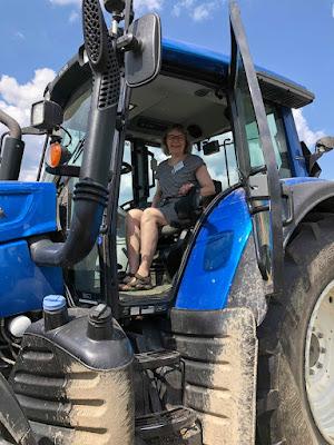 Matleena istuu korkealla suuren sinisen traktorin ohjaamossa.