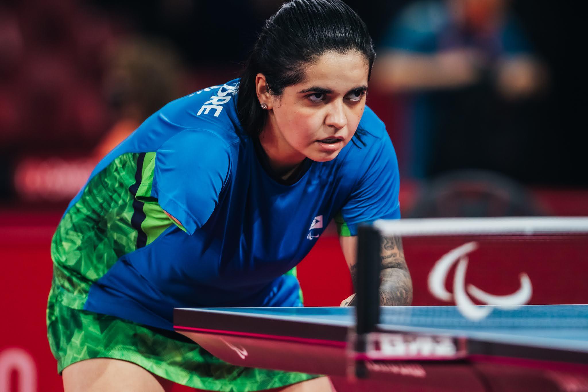 Bruna Alexandre, de azul, está com as costas flexionada em frente à mesa e tem a raquete na mão, com olhar sério