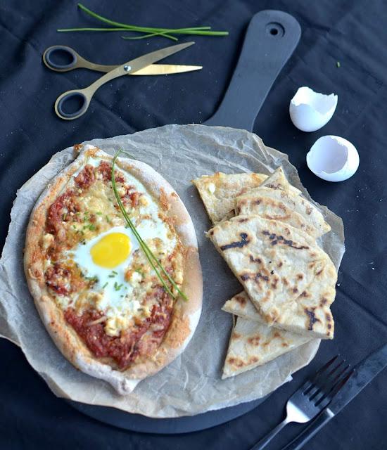 Khachapuri được cho là xuất hiện tại Gruzia từ thế kỷ XVI, khi những người lính La Mã đến vùng Biển Đen và mang theo công thức bánh mì nướng của họ. Khachapuri được coi như là họ hàng với pizza, lý do vì bột bánh rất giống và bánh cũng có phần nhân ngập phô mai như pizza. Bột bánh Khachapuri cũng là bột bánh mì tương tự pizza, gồm bột mì, nước, chút muối và men nở.
