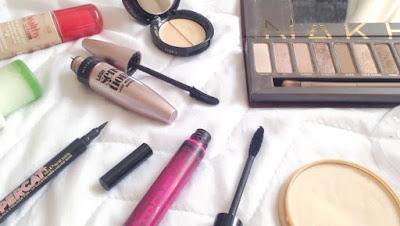 makeup flatlay of mascara, powder, foundation, eyeshadow and eyeliner