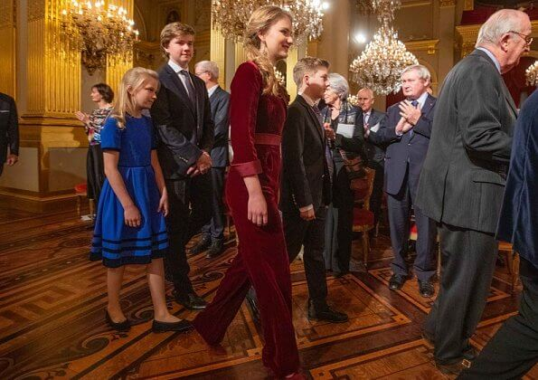 Queen Mathilde wore a floral print gown by Dries Van Noten. Crown Princess Elisabeth wore a velvet-satin jumpsuit by DVF