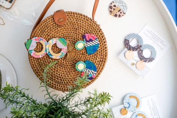 circular paper earrings displayed on woven handbag