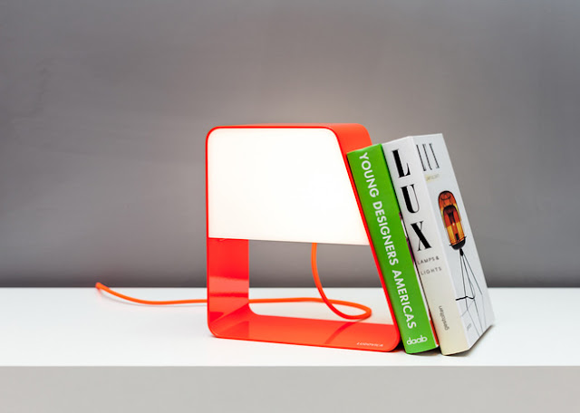 Uma luminária em forma de trapézio de cor laranja, sendo que uma parte dela é vazada e a outra com um espaço pra luz. Ou seja, a peça é uma luminária, mas também permite apoiar livro devido ao seu formato.