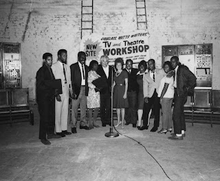 A photograph of a group of figures standing in front of a banner for a TV and Theatre workshop.