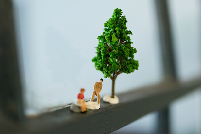 Two minute human figures and a tree on the crossbar of a windowfarme.