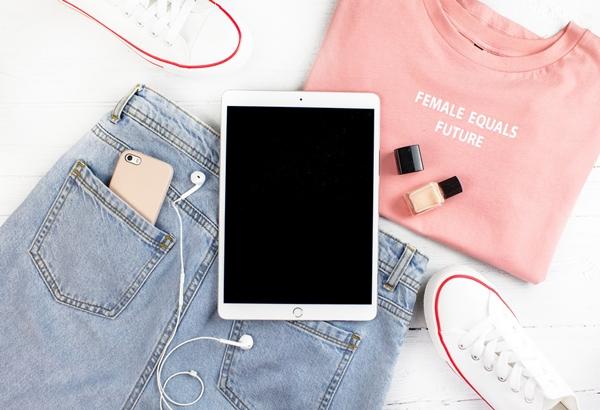 Flatlay de um tablet com fone plugado sobre uma blusa rosa e uma calça jeans