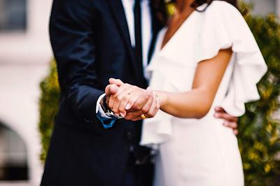 Foto preboda de novios, ella con un vestido blanco y enseñando el anillo