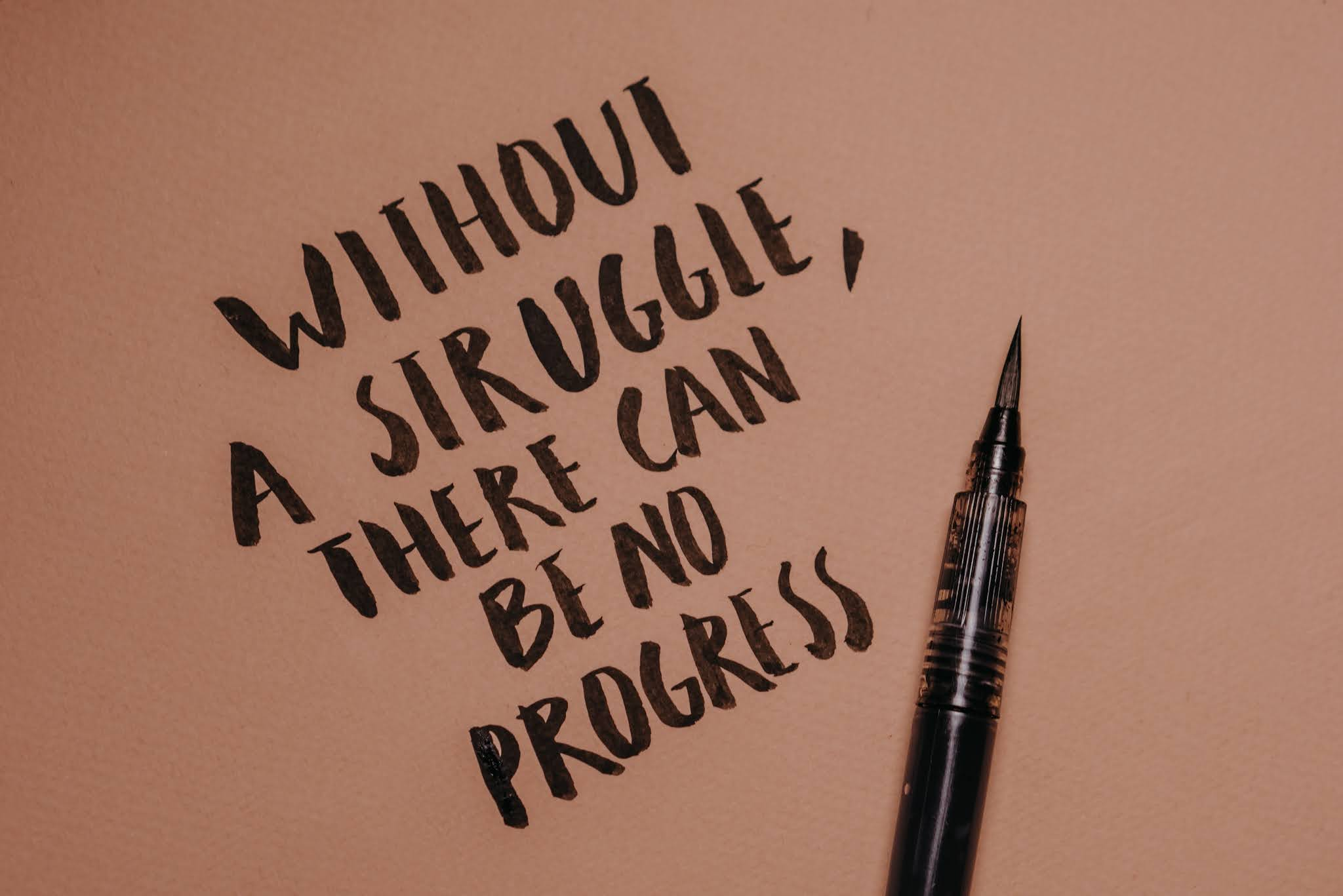 calligraphy on paper - with phrase 'without a struggle there can be no progress'