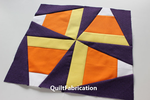 four yellow orange white candy corn quilt blocks with purple background by QuiltFabrication