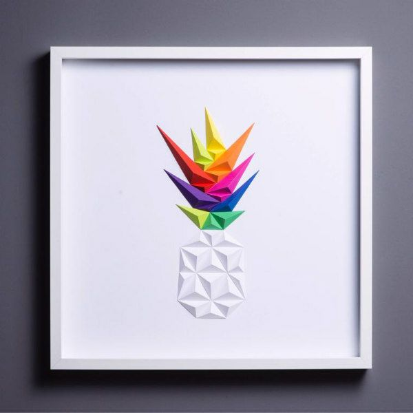 3D folded white paper pineapple with colorful leaves in square white frame hanging on wall