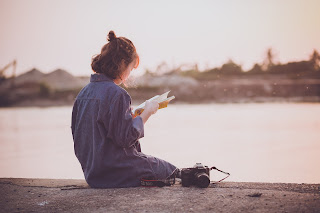 woman reading by water