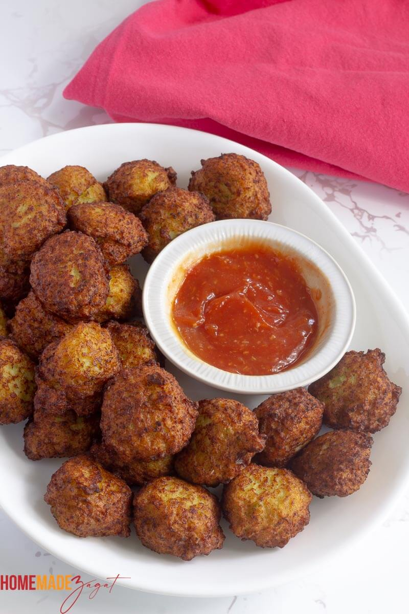 Golden fried conch fritters on a white plate with a bowl of red dipping sauce