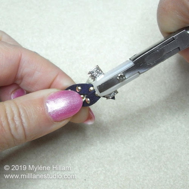Clamping the ribbon crimp with nylon jaw pliers.