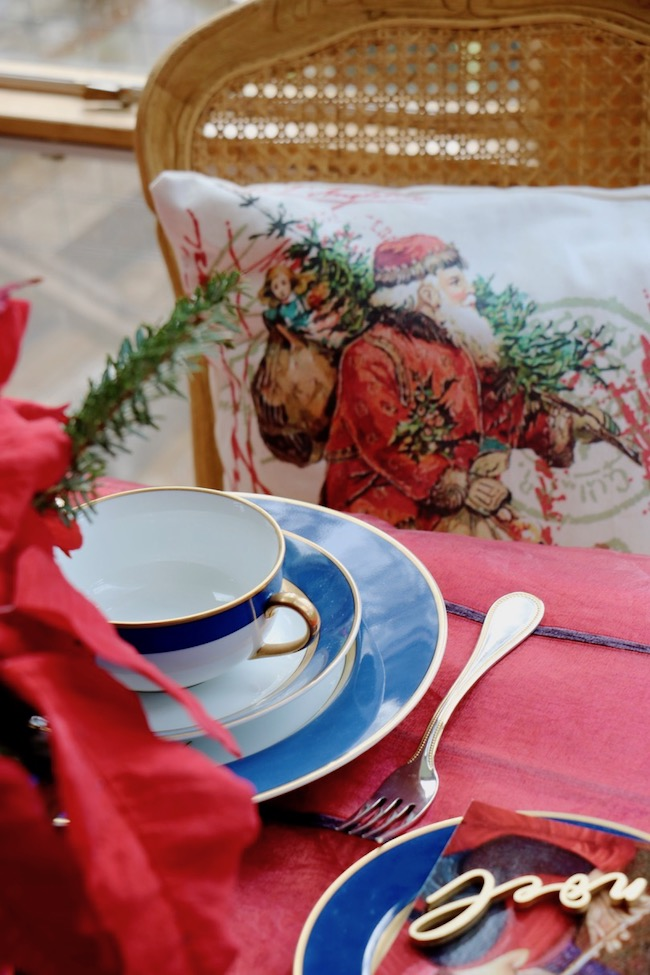 Gold rimmed china, gold beaded flatware, and gold painted laser cut NOEL words accent the deep jewel colors on the Christmas Red and Navy Blue Table Setting