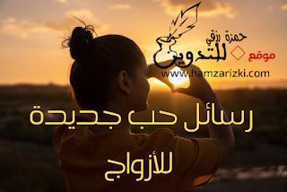 رسالة حب قصيرة مكتوبة على صورة فتاة مغربية ترسم قلب بيدها أمام غروب الشمس وتبتسم