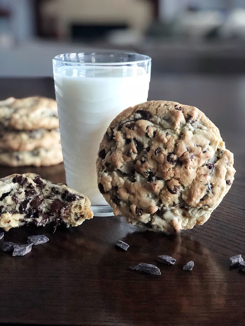 large chocolate chip cookies on the table with a glass of milk