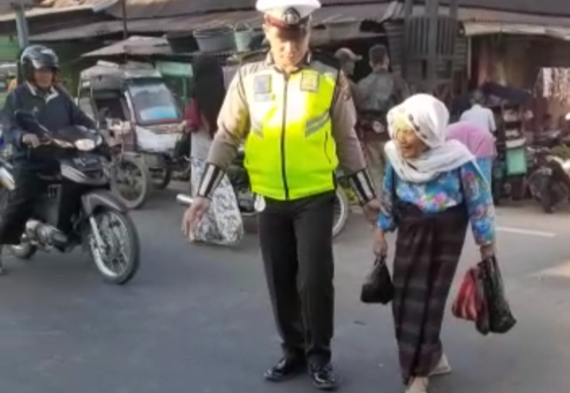 Personil Sat Lantas Polres Madina Bantu Nenek Hendak Menyeberang Jalan