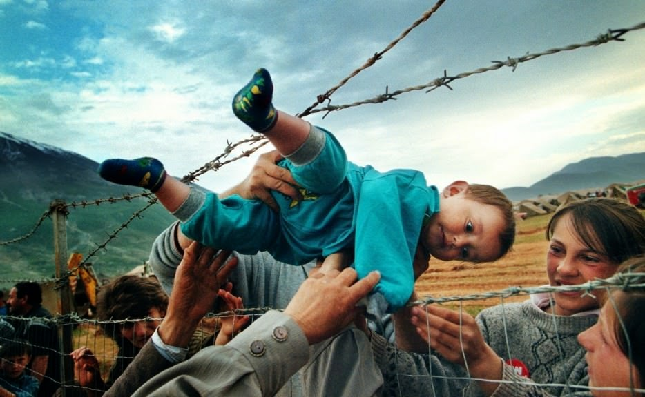 Agim Shala is passed through a barbed wire fence to his grandparents at a camp for refugees of the Kosovo War. - The 63 Most Powerful Photos Ever Taken That Perfectly Capture The Human Experience