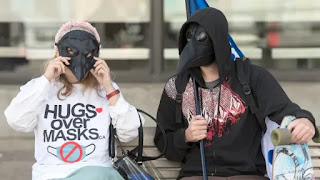 People wear masks during a demonstration opposing the mandatory wearing of face masks and coverings in Montreal earlier this month. (Graham Hughes/The Canadian Press)