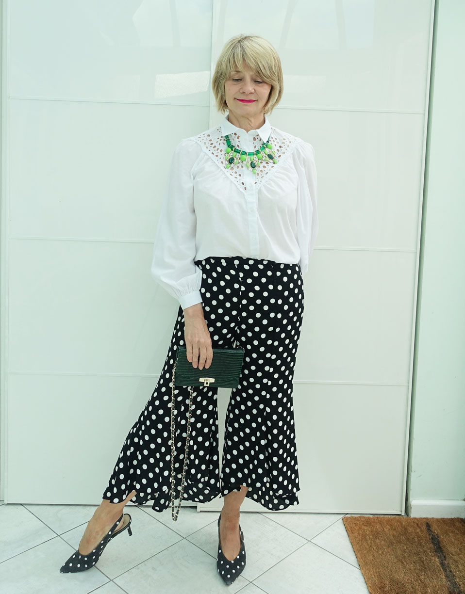 A retro necklace adds color to a black and white outfit of fluted bottom cropped polka dot trousers, white broderie blouse and polka dot sling back shoes, worn by Gail Hanlon from over-50s style blog Is This Mutton