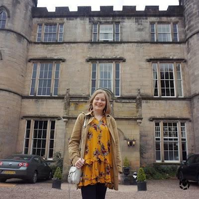 awayfromtheblue Instagram | melville castle hotel entrance mustard floral dress trench coat for spring