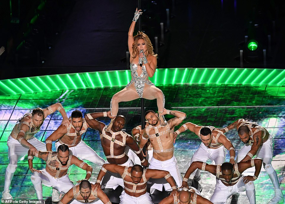 Jennifer Lopez is surrounded by hunky men as she pole dances during the 2020 Super Bowl Half Time Show